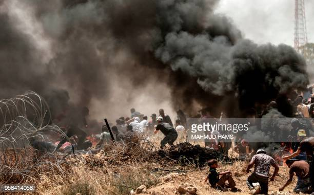 TOPSHOT Palestinians clash with with Israeli forces near the border between the Gaza strip and Israel east of Gaza City on May 14 as Palestinians...