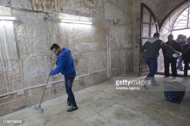 Palestinians clean the ground prior to perform Friday prayer inside the AlRahma Gate at AlAqsa Mosque Compound after the continued closure by Israeli...