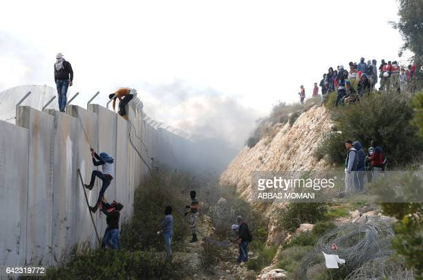 TOPSHOT CORRECTION Palestinians climb on top of Israel's controversial separation wall between the West Bank village of Bilin near Ramallah and the...