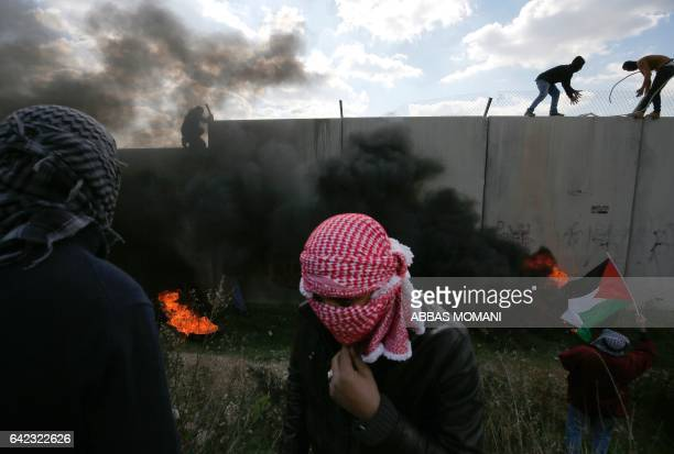 TOPSHOT Palestinians climb on top of Israel's controversial separation wall between the West Bank village of Bilin near Ramallah and the Israeli...