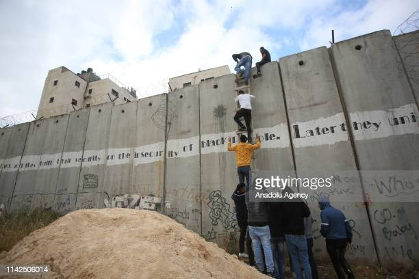 Palestinians climb the ladder to cross the separation wall and reach Jerusalem in order to perform the first Friday Prayer of Islamic holy month of...