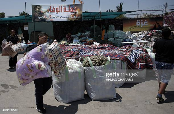 Palestinians collect goods and blankets in East Jerusalem on August 14 to be sent and distributed with the Red Cross to people in need in the Gaza...