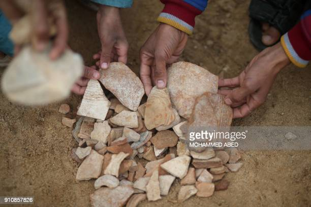 Palestinians collect pottery fragments at a freshlydiscovered cemetery in a house garden in the town of Beit Hanun in the northern Gaza Strip on...