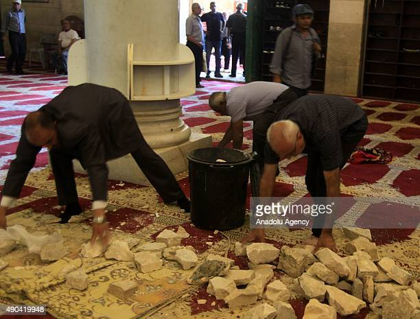 Palestinians collect the stones inside alQibli mosque in Al Aqsa Mosque compound after an Israeli riot police intervention while a group of...