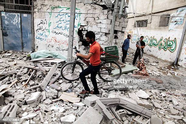 Palestinians collect their objects among the ruins as a result of Israeli air strike in Gaza City Gaza on 18 July 2014 260 people died and 1980...