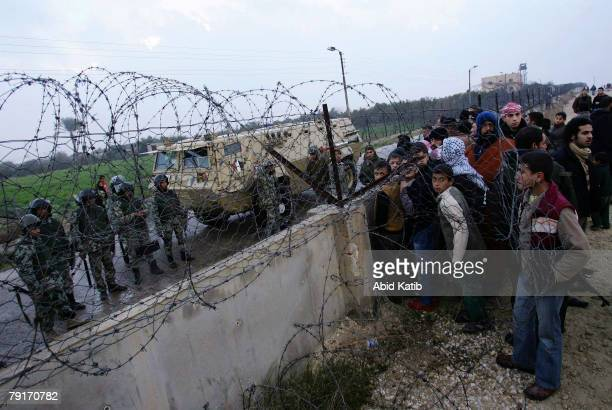 Palestinians cross the Rafah border into Egypt over a barrier destroyed by masked Palestinian militants overnight January 23 2008 in Rafah Gaza Strip...