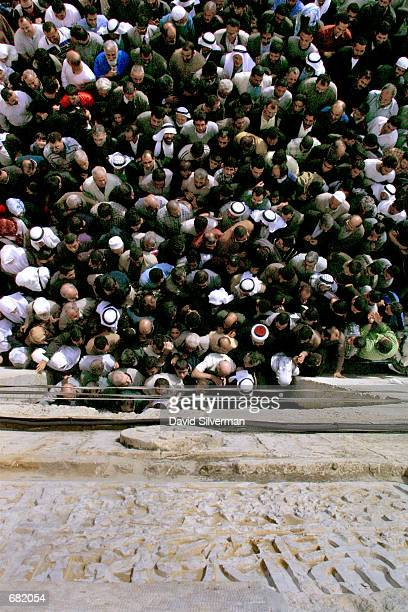 Palestinians crowd around one of the ancient gates of Jerusalem's Old City November 16 2001 as they leave the Temple Mount following the first Friday...