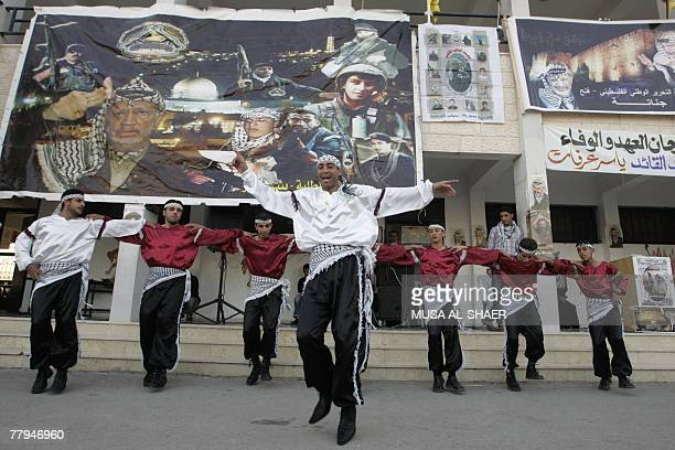 Palestinians dance during a ceremony to mark the third anniversary of late leader Yasser Arafat's death and the 19th anniversary of the 1988 symbolic...