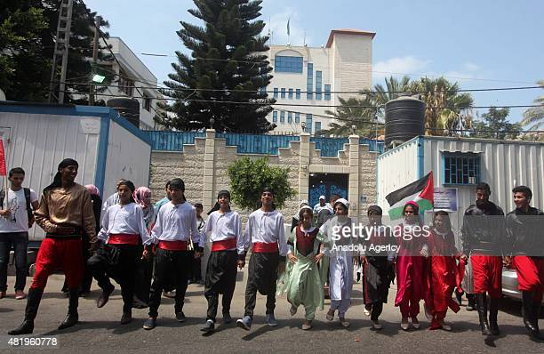 Palestinians dance in traditional Palestinian clothing during a protest in Gaza City Gaza on July 25 2015 Hundreds of Palestinians gathered in front...
