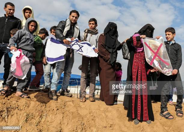 Palestinians demonstrate with crossedout posters depicting Israeli Prime Minister Benjamin Netanyahu and US President Donald Trump during a tent city...