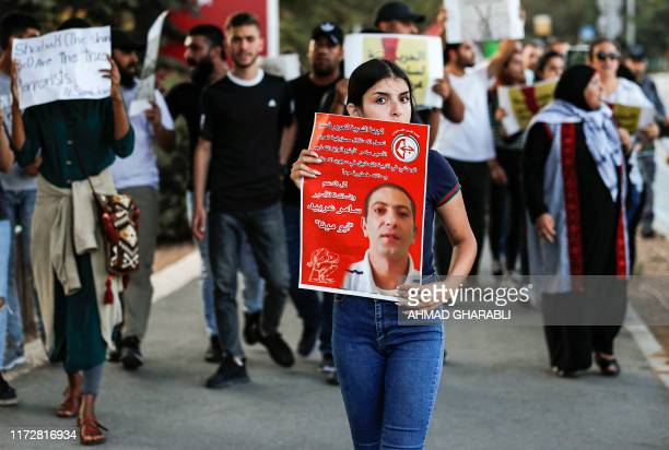 Palestinians demonstrate with signs in support of and with the pictures of Samer alArbeed a Palestinian arrested by Israeli on suspicion of leading a...