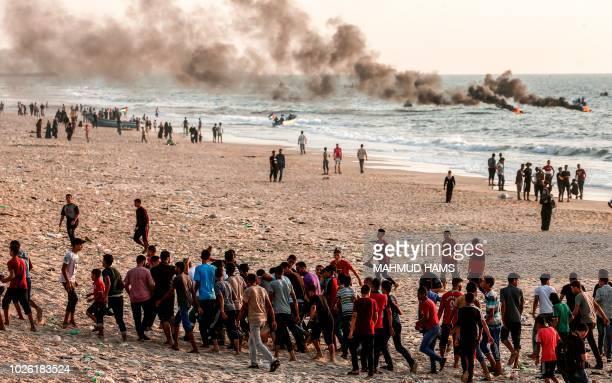 Palestinians demonstrators carry away an man who was injured during clashes with Israeli forces on a beach along the Gaza sea barrier on the border...