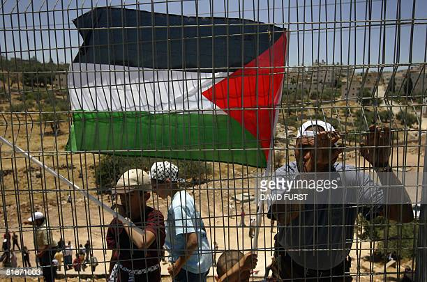 Palestinians demonstrators hold up their national flag along a fence separating them from a road used by Israeli vehicles during a protest marking...