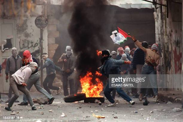 Palestinians demonstrators throw rocks 29 January 1988 in Nablus at Israeli soldiers during violent protests gainst the Israeli occupation The...