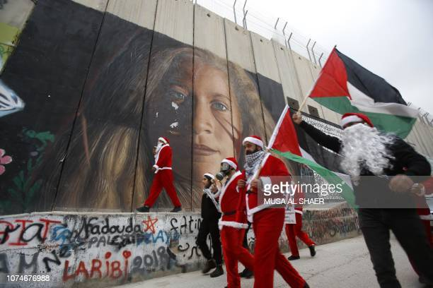 TOPSHOT Palestinians dressed as Santa Claus in Bethlehem hang signs on a mural painting of Palestinian militant Ahed Tamimi on Israel's controversial...