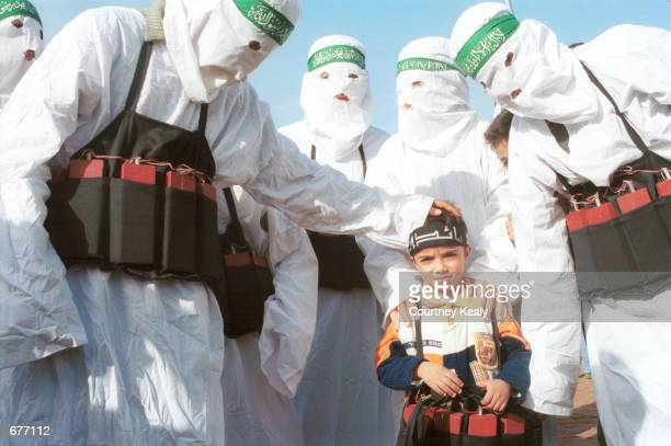 Palestinians dressed as suicide bombers put fake explosives on a small child December 9 2001 after marching in commemoration of the 14th anniversary...