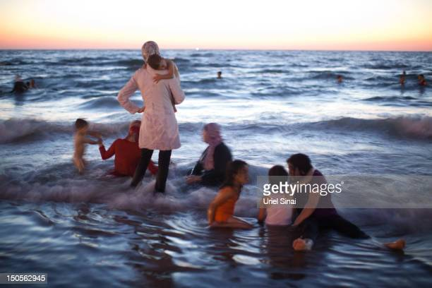 Palestinians enjoy a day at a beach during Eid alFitr which marks the end of the holy month of Ramadan on August 21 2012 in Tel Aviv Israel According...