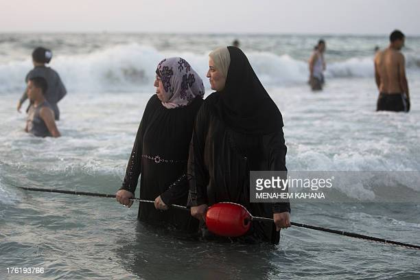 Palestinians enjoy the Tel Aviv beach a day after the EidalFitr festival marking the end of the holy fasting month of Ramadan on August 11 2013 Tens...