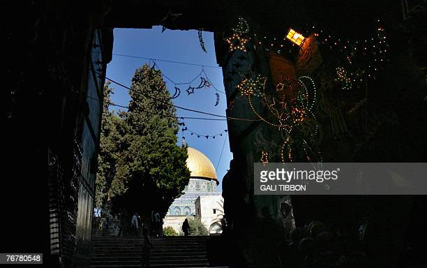 Palestinians enter the AlAqsa Mosque compound in Jerusalem's Old City as Ramadan decorations hang in nearby shop 16 September 2007 The world's 12...