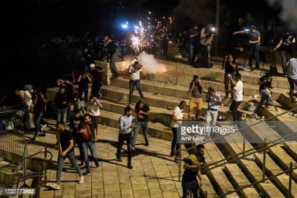 Palestinians escape from a stun grenade fired by Israeli police officers during clashes at Damascus Gate during the holy month of Ramadan on May 8,...