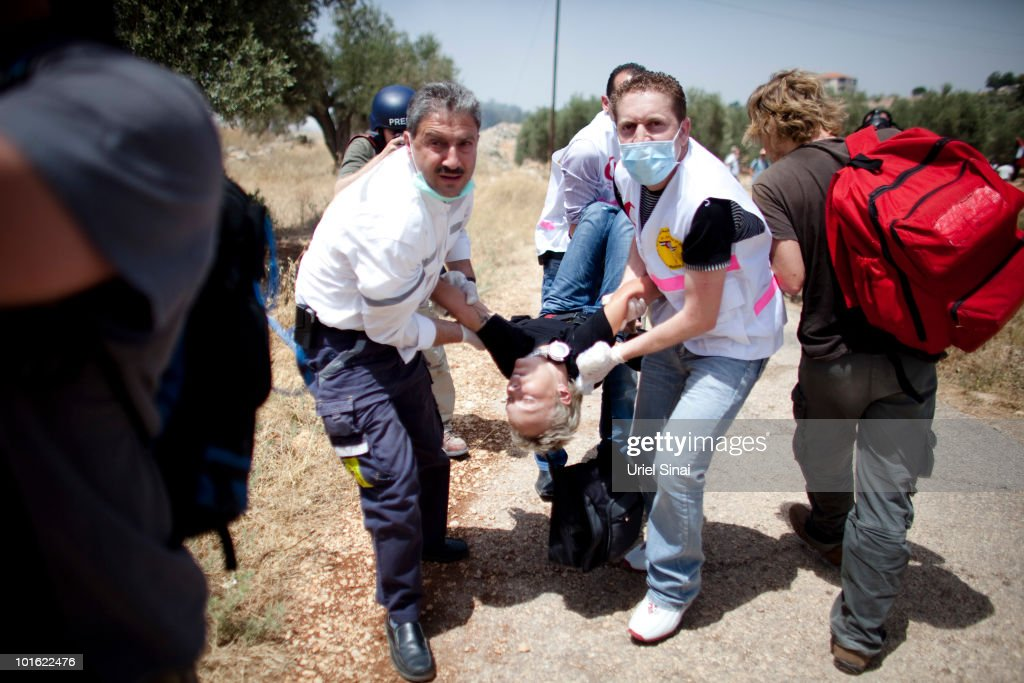 Palestinians evacuate a woman after she inhaled tear gas near an Israeli barrier, as they object to Israel's attack on a Gaza aid flotilla earlier this week, on June 4, 2010 in Bil'lan, the West Bank. Israel has faced international criticism over the deadly raid on May 31, aboard a ship carrying humanitarian aid to the Gaza Strip.