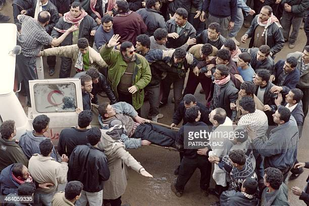 Palestinians evacuate an injured fellow on February 25 after the Cave of the Patriarchs massacre carried out by Jewish settler Baruch Goldstein who...