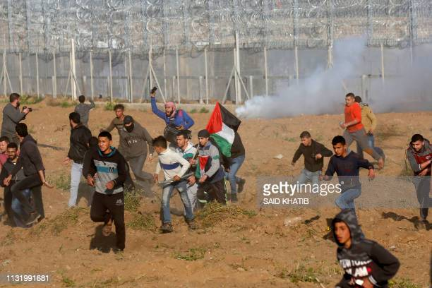 Palestinians flee from tear gas during a protest by the barbedwire fence with Israel east of Gaza City on March 22 2019