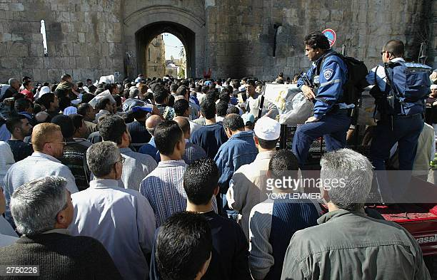 Palestinians flock to the AlAqsa mosque compound in east Jerusalem 21 November 2003 as Israeli police watch over during the last Friday noon prayers...