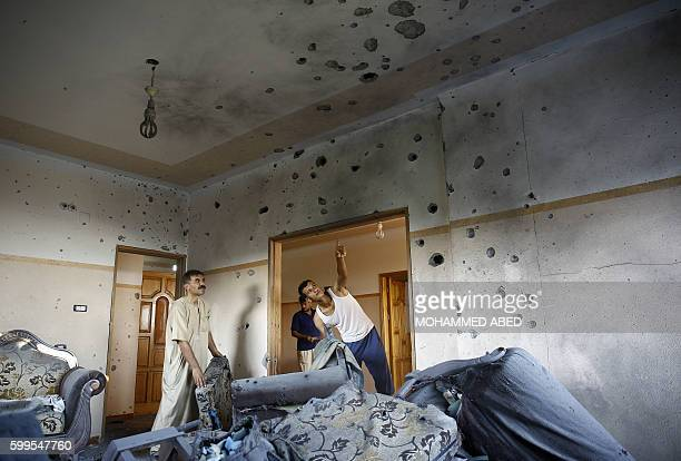 TOPSHOT Palestinians from the alShanti check a shrapnel riddled wall after their house was hit on September 6 2016 in Beit Hanun in the northern Gaza...