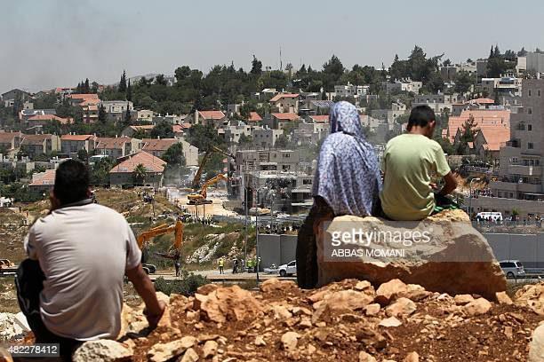 Palestinians from the Jalazoun refugee camp look at bulldozers demolishing the socalled Dreinoff buildings under an Israeli High Court ruling in the...