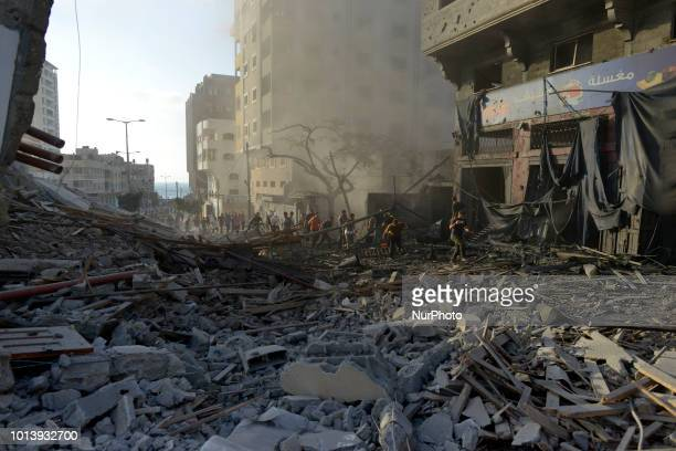 Palestinians gather around a building after it was bombed by an Israeli aircraft in Gaza City August 9 2018