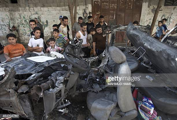 Palestinians gather around a burnt car of the company of electricity that was hit by an Israeli air strike in Beit Lahia City on August 26 2014 in...