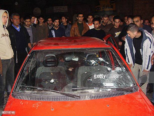 Palestinians gather around a car that carried four militants killed by an Israeli undercover forces in the West Bank town of Bethlehem on March 12...