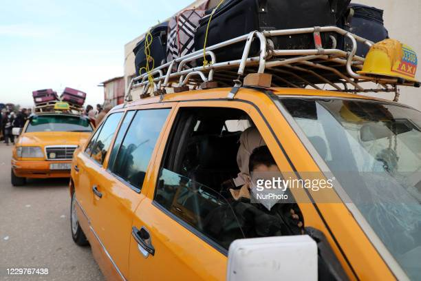 Palestinians gather around cars loaded with suitcases as passengers wait to leave Rafah border crossing with Egypt which was reopened partially amid...