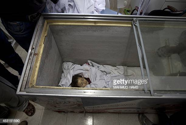 Palestinians gather around the body of Raghad Masoud on August 4 which is being stored in a freezer previously used to store icecream because the...