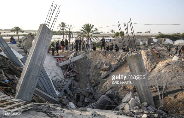 Palestinians gather around the remains of a house destroyed in an Israeli air strike at Khan Yunis in the southern Gaza Strip November 13, 2019. -...