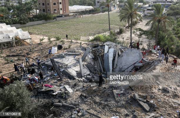 Palestinians gather around the remains of a house destroyed in an Israeli air strike in Khan Yunis in the southern Gaza Strip November 13, 2019. -...