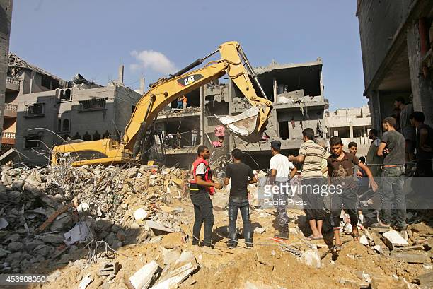 Palestinians gather around the rubble of a destroyed building, following according to Hamas the killing of three of its senior commanders who were...