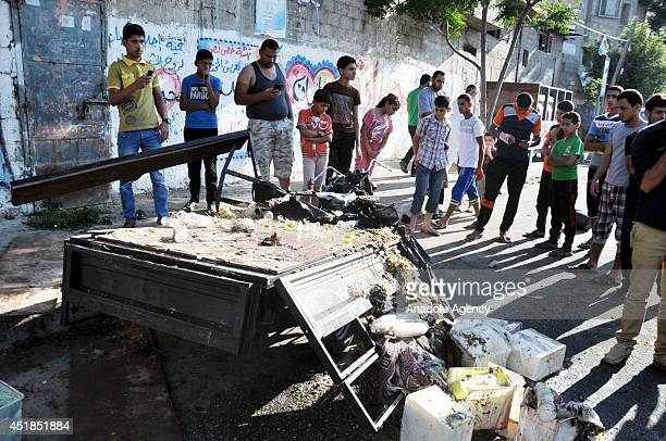 Palestinians gather around the wreckage of a tuk-tuk after it was hit by an Israeli strike in Gaza City, on July 8, 2014. The toll from a fresh...