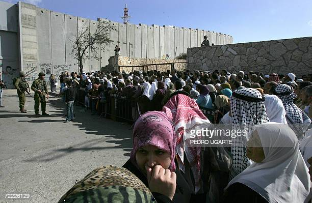 Palestinians gather at a checkpoint integrated into the controversial West Bank separation barrier on the outskirts of the biblical town of Bethlehem...