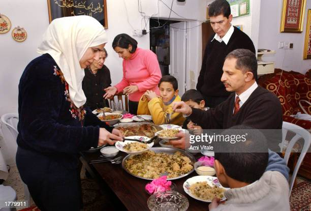 Palestinians gather for a meal on the second day of the Muslim holiday of Eid alAdha or feast of sacrifice February 12 2003 in the West Bank city of...
