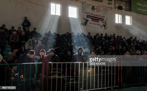 Palestinians gather in a makeshift station in Khan Younis in the southern Gaza strip on December 16, 2017 as they await clearance to take a bus to...