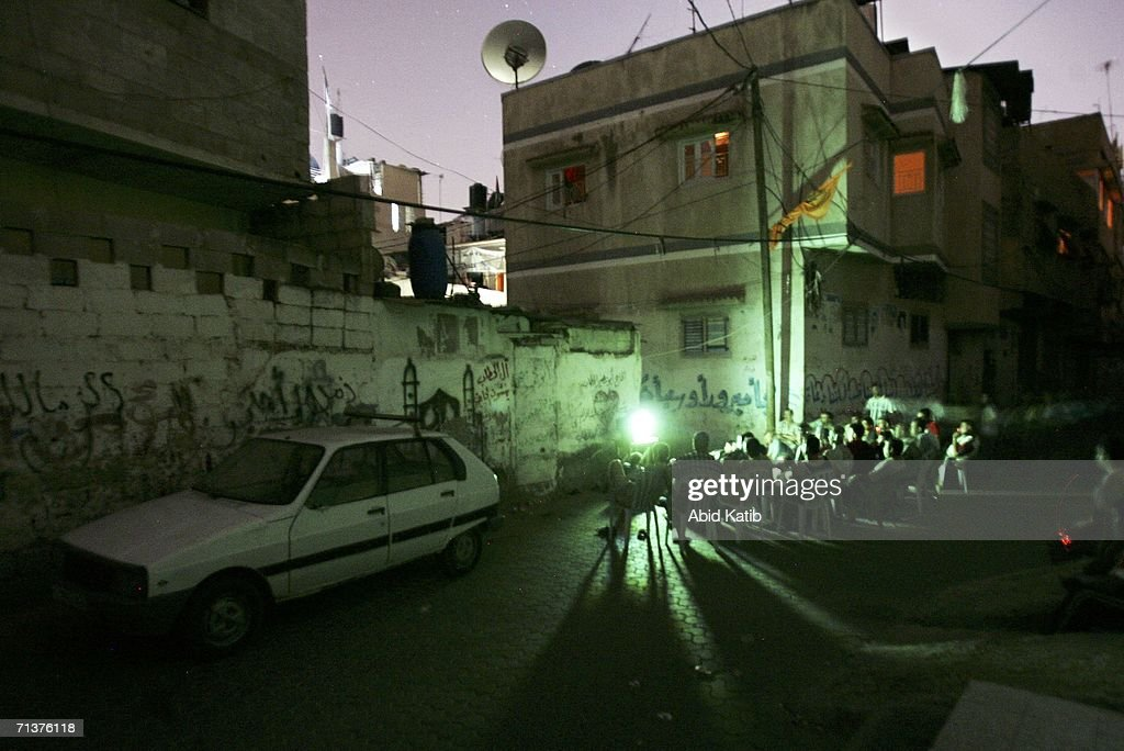 Palestinians gather in front of a television powered by a generator