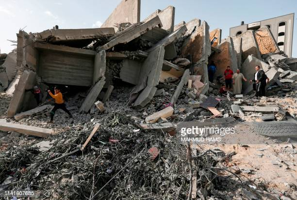 Palestinians gather on May 6, 2019 amidst the rubble of a building that was destroyed during Israeli airstrikes on Gaza City. - Palestinian leaders...