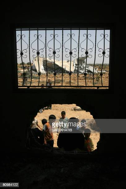 Palestinians gather to inspect the damage done to a home as a demolished house sits in the background following an Israeli operation in the Southern...