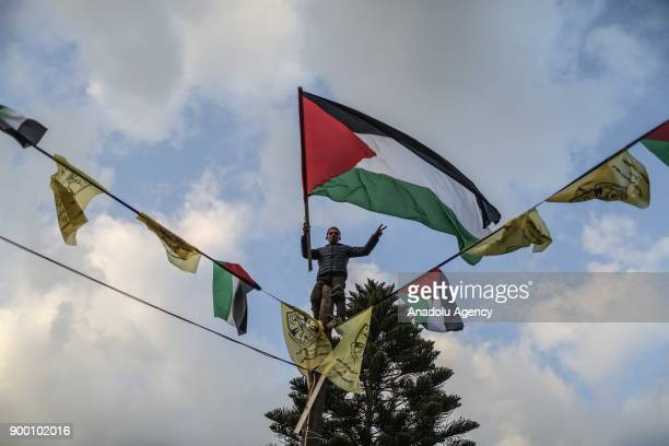 Palestinians gather to mark the 53th Foundation anniversary of Palestinian Fatah movement at Unknown Soldiers Monument in Gaza City Gaza on December...