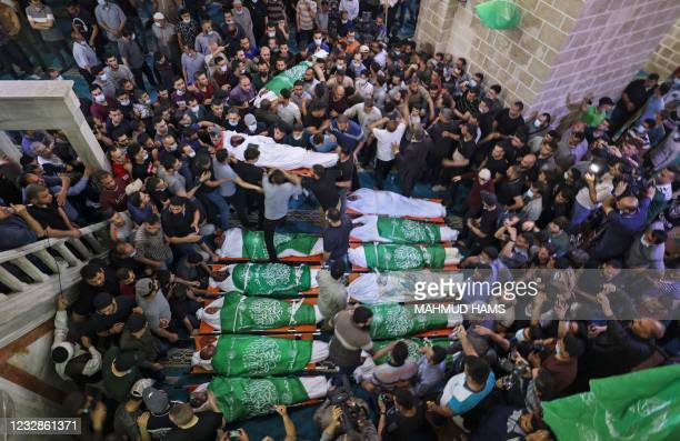 Palestinians gather to pray around the bodies of 13 Hamas militants, killed in Israeli air strikes, during their funeral at the al-Omari mosque in...