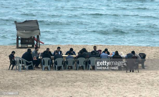 "Palestinians gather to share the ""iftar"" fast-breaking meal consumed by Muslims at sunset during the holy fasting month of Ramadan, along the shore..."