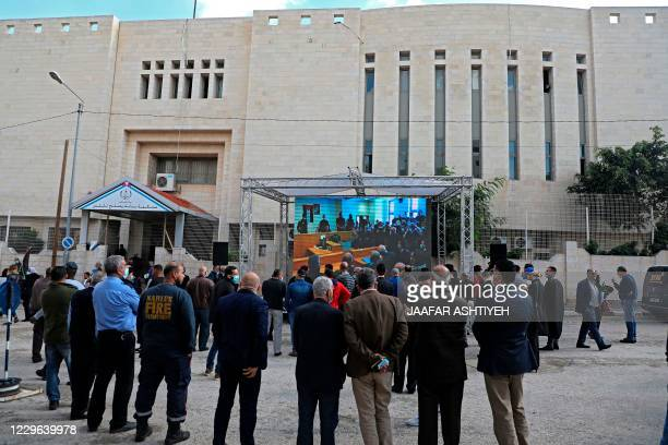 Palestinians gathering outside the Nablus Court of First Instance and Reconciliation building watch proceedings on a giant screen as a judge opens...