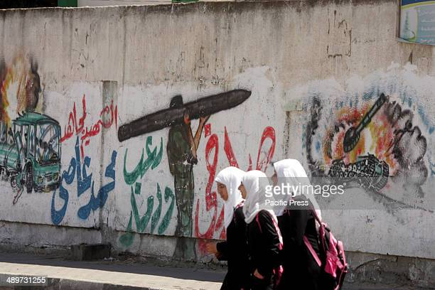 """Palestinians girls, in Rafah in the southern Gaza Strip, walk next to a wall drawing/mural of a militant carrying a rocket. Nakba, or """"catastrophe"""",..."""